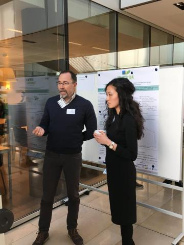Dr Jenny Lieu, TRANSrisk's co-principal investigation, and Prof Francesco Bosello, coordinator of COACCH, discussing potential synergies (detail: TRANSrisk poster at background)